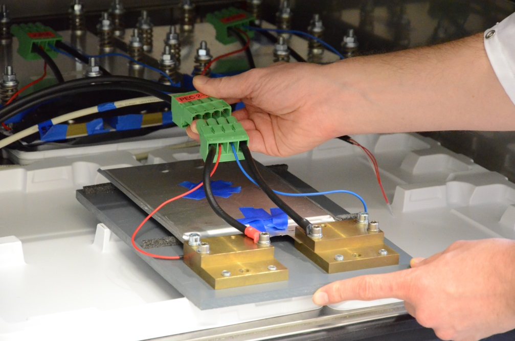 Batteriezelle, die gerade in einen Klimaschrank gelegt und an die Messelektronik angeschlossen wird. Im Hintergrund zwei weitere, zwischen Aluminiumplatten verspannte, Testzellen.